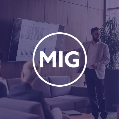 White MIG logo, with a corporate presentation in the background and a representative pointing to a large screen